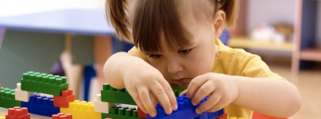 Little girl play with building bricks in preschool