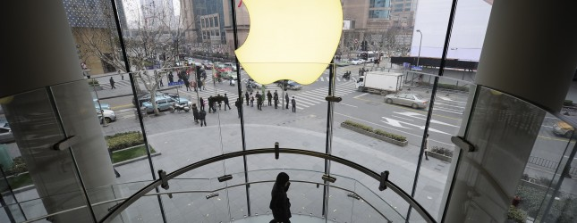 A customer walks under an Apple logo sig