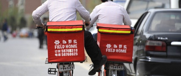 Two workers ride bicycles to deliver fas