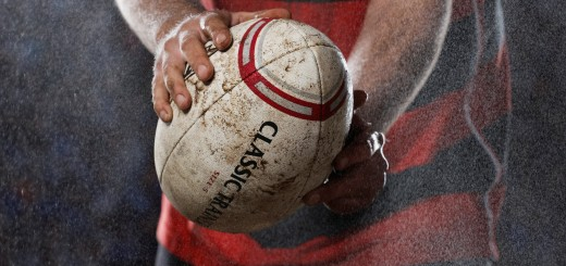 Rugby player holding ball in rain, mid section