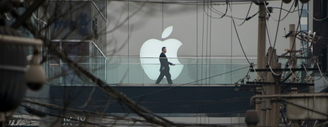 "A man walks past an Apple logo displayed above a street at a shopping mall in Beijing on March 29, 2013. Apple is to face ""strengthened supervision"" from China's consumer watchdogs, state media reported, as the US computer giant is hit by a barrage of negative publicity in the country. AFP PHOTO / Ed Jones        (Photo credit should read Ed Jones/AFP/Getty Images)"